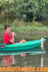 Angler in a kayak reels in his catch