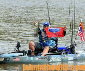 McElroy holds a bass and displays a tournament flag from his kayak