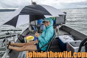 Abbey tries to avoid some of the rain on the boat with her rain jacket and umbrella