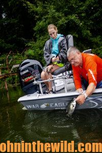 Two anglers work together to pull in a fish