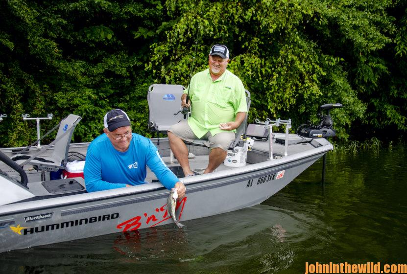 Two anglers work to get a fish out of the water