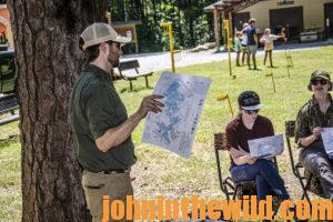 An instructor goes over a map of where students can hunt