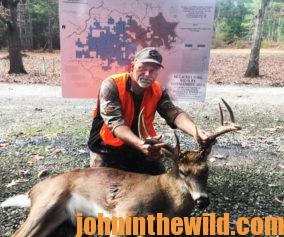 A hunter with his downed deer