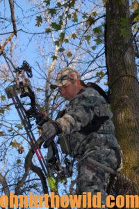 A hunter takes aim from his tree stand