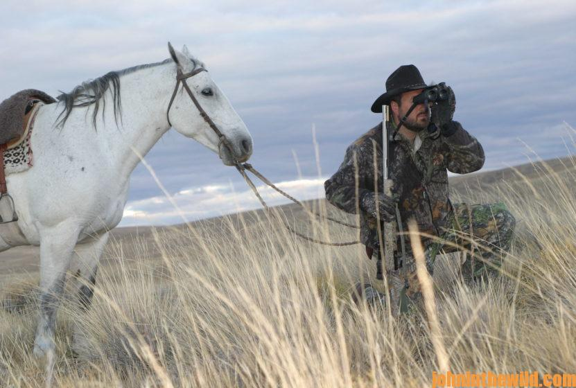 A hunter scouts out the area with binoculars while holding his horse's reins