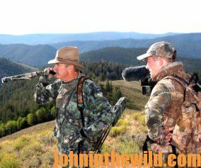 Two elk hunters in the field: one calling in an elk while the other records