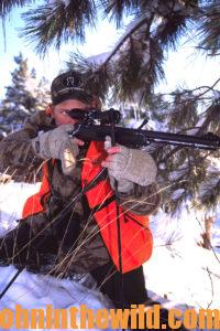 A hunter aims with his rifle