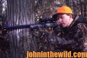 A hunter aims at his target with his rifle