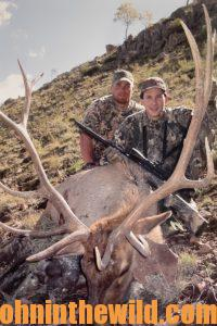 Two hunter pose with their downed elk